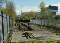 View through the fence at the end of the line at Powderhall refuse depot in 1999. Note the anchored yellow box for the looped steel cable, used to position the container flats during loading and unloading [see image 12012].<br><br>[Ewan Crawford&nbsp;//1999]