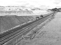 Located near Midcalder Junction, the large shale bing associated with the Oakbank Oil Works was often referred to as 'Contentibus Bing'. In June 1984 it was in the process of being reclaimed for motorway construction with rail being the means of delivery. The entrance to the siding can just be made out in the right background.<br><br>[Bill Roberton&nbsp;23/06/1984]