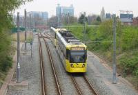 <I>Over the top!</I> Two 3000 series trams heading for East Didsbury drop down the steep slope alongside Old Trafford Metrolink Depot to regain the original Midland Railway formation. Behind them is a depot access point and beyond that the Trafford Bar junction with the Altrincham line and the <I>diveunder</I> for Manchester bound trams. [See image 51062]<br><br>[Mark Bartlett&nbsp;24/04/2015]