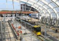 The new three line Metrolink platforms arrangement at Victoria is now taking shape, and trams are calling again although work is not yet finished. With the roof cladding now in place, a double tram for Bury pulls into the centre road on 20th April 2015. [See image 49339] for the same location six months earlier. <br><br>[Mark Bartlett&nbsp;20/04/2015]