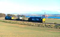 DRS 37218 and 37605 top and tail the nuclear flask train southwards between Invergordon and Alness on 1 May 2015. In the background the Cromarty Firth, with a couple of drilling platforms awaiting a recall to the North Sea.<br><br>[John Gray&nbsp;01/05/2015]