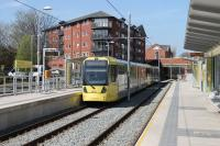 Metrolink 3011 calls at Didsbury Village on an East Didsbury to Rochdale service in April 2015. Didsbury railway station, previously just beyond the bridge, closed in 1967 but rail borne services returned 46 years later with the opening of the East Didsbury tram line in 2013. <br><br>[Mark Bartlett&nbsp;20/04/2015]
