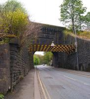 Looking up Stoneclough Road in Kearsley under the railway bridge on 10 May 2015. The station entrance is beyond the bridge on the right. There has been some significant bracing applied to the retaining walls on this side of the bridge.<br><br>[John McIntyre&nbsp;10/05/2015]