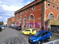 The Dryden Street facade of Edinburgh Corporation Tramway's former Shrubhill depot and works in May 2015. Having survived demolition for so long it is a pity this building is a target for graffiti (sorry, street art). Added to the scene are some cars which will cause nostalgic head-shakings in future decades.<br> <br><br>[David Panton&nbsp;11/05/2015]