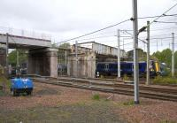 A class 380 on an Ayr - Edinburgh service passes under the last remaining section of the Old Mill Road bridge across the West Coast Main Line at Cambuslang on 22nd May 2015. To the left, the first section of the replacement bridge is now in place across the Cathcart line [see image 50259].<br><br>[Colin McDonald&nbsp;22/05/2015]