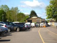 Looking west along the car park at Sherborne Station on 12 May, with the former goods shed at the far end. A large replica totem shows it is now called <I>The Railway Shed</I> and being used by a fibreglass fabricator. <br><br>[David Pesterfield&nbsp;12/05/2015]