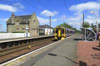 The Caledonian Railway station building at Kirknewton provides an interesting contrast in style with the contemporary bike shelter on the opposite platform as 158724 passes through with an Edinburgh Waverley to Glasgow Central (via Shotts) express.<br><br>[Malcolm Chattwood&nbsp;26/05/2015]