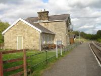 Looking east along the platform at Redmire Station on the Wensleydale Railway, with the well maintained station building now used by the Scouting Organisation. Sidings for the occasional loading or off-loading of military vehicles to or from Catterick Garrison are located behind the camera.<br><br>[David Pesterfield&nbsp;25/05/2015]