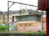 The old Muirhouse Junction signal box seen from the door of a train standing in Pollokshields East station in August 2006. The tenements of Darnley Street form the backdrop. <br><br>[John Furnevel&nbsp;11/08/2006]