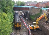 Looking towards Farnworth station from above the tunnel portals on 2 June 2015 as a Hazel Grove to Preston service passes. On the right the excavator is removing soil from the new track alignment.<br><br>[John McIntyre&nbsp;02/06/2015]