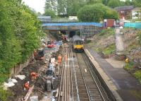 A Manchester Victoria to Clitheroe service exits the smaller Farnworth Tunnel and passes through the temporarily closed station on 2 June 2015. On my last visit the Up platform was being excavated to allow for realignment. The blockwork wall for the new alignment is now starting to appear on the left but the major change will be the removal of the road bridge in the background.<br><br>[John McIntyre&nbsp;02/06/2015]