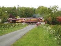 DB palindromic numbered 66066 opens up as it crosses Betteras Hill Road level crossing heading south shortly after leaving Milford Junction sidings on 18 May with a mixed rake of refurbished DB red and un-refurbished ex National Power bogie coal wagons.<br><br>[David Pesterfield&nbsp;18/05/2015]