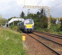 ScotRail 334003 slowing for the stop at Cardross on 31 May 2015 with a service for Helensburgh Central. Photographed looking west from Bainfield foot crossing.<br><br>[John McIntyre&nbsp;31/05/2015]