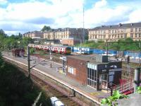View over Pollokshields East station from Albert Drive in August 2006. In the background a northbound train is passing the disused signal box at Muirhouse Junction heading for Glasgow Central.<br><br>[John Furnevel&nbsp;11/08/2006]