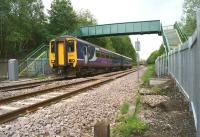 Northern 156451 passes under the relatively new footbridge to the north of Kearsley station on 2 June 2015. The footbridge replaced the foot crossing, the remains of which are in the centre foreground (a wooden post from the wicket gate and the concrete ramp) in March 2015.<br><br>[John McIntyre&nbsp;02/06/2015]