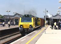 Freightliner 70014 makes its presence felt (and heard) as it accelerates an eastbound container train through the platforms of Didcot station on 11 June 2015.<br><br>[Peter Todd 11/06/2015]