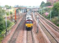 Longannet empties heading back to Hunterston in August 2006 behind EWS 66145 passing Rutherglen Central Junction. The train is about to run under the pedestrian walkway linking Rutherglen station with Victoria Street.<br><br>[John Furnevel&nbsp;15/08/2006]
