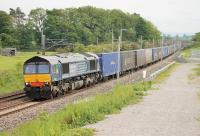 DRS 66303, with a Daventry to Coatbridge container service, runs north between the bridges at Elmsfield on 16th June 2015. The land in the foreground has been made into an engineers' access point with a ramp leading down from the bridge embankment.  <br><br>[Mark Bartlett&nbsp;16/06/2015]