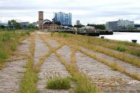 Looking along the former Yorkhill Quay towards the SECC from near the Riverside Museum on 22nd June 2015. The course of the rails and pointwork from the former Stobcross branch sidings is shown by the weeds growing in the rails.<br><br>[Colin McDonald&nbsp;22/06/2015]