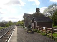 Platform view west through Redmire Station on the Wensleydale Railway in May 2015, showing the lengthy run round loop on the left and the loading sidings for military vehicles to and from Catterick Garrison on the right beyond the platform end. <br><br>[David Pesterfield&nbsp;25/05/2015]
