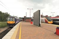319380, in new <I>Northern Electrics</I> livery, makes a connection with two Pendolinos at Wigan North Western on 25 June, prior to returning to Liverpool Lime Street via St Helens. Although these 4-car former <I>Thameslink</I> EMUs have been around for some time they have been refurbished and are a great improvement on the 2-car Pacers they have replaced on these services. <br><br>[Mark Bartlett&nbsp;25/06/2015]