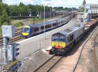 DRS 66423 passes ScotRail 170 and 158 units stabled in bay platform 5 at Perth station on 28 June 2015 with a Moy - Millerhill spent ballast train.<br><br>[Bill Roberton&nbsp;28/06/2015]