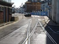 Looking along Custom House Quay from the junction with The Quay and Esplanade in May 2015, showing the check railed points on the disused Weymouth Tramway at the approach to the harbour station (behind the camera).<br><br>[David Pesterfield&nbsp;12/05/2015]