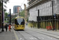 Double track working has been reinstated along Balloon St between Manchester Victoria and Shudehill. Additionally, all the setts are back in the roadway and the <I>Heras</I> fencing has been removed. Brand new tram 3099 drops down towards Victoria heading for Rochdale on 25th June 2015. [See image 48387] for the same location during the previous summer. <br><br>[Mark Bartlett&nbsp;25/06/2015]