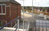 The new pedestrian entrance to Newtongrange station giving access from the overbridge on the A7 Murderdean Road. The building on the left was part of the rail served Dean Oil Works which once occupied the station site. Photographed through security fencing on 17 July 2015. [See image 51987]<br><br>[John Furnevel&nbsp;17/07/2015]