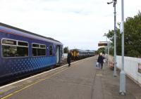 Platform scene at Girvan on 12 August 2015. The Conductor / Guard of the 09.38 Glasgow to Stranraer waits to give the right-away as the 10.10 Stranraer to Kilmarnock (change at Ayr for the 11.52 EMU to Glasgow Central) departs northward.<br><br>[Colin Miller&nbsp;12/08/2015]