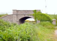 Granite bridge over the trackbed of the Peterhead Quarry Railway at Lendrum Terrace, two and a half miles south of the Harbour and Prison at Peterhead. The line ran from Stirlinghall Quarry, south of this bridge to the Harbour of Refuge, carrying granite for the great breakwaters and convict labour to the quarry. The bridge, as other structures on the line, built to exacting Admiralty design standards and an example of exceptional craftsmanship - far above what would be expected of an 'industrial' railway.<br><br>[Brian Taylor&nbsp;20/06/2015]