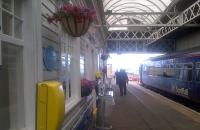Scene at Stranraer on 26 August 2015, with the 1443 service to Kilmarnock at the platform and silk flowers by Louis Wall enlivening the station.<br><br>[John Yellowlees&nbsp;26/08/2015]