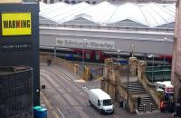 The Calton Road entrance to Waverley, photographed looking south from Waterloo Place on 27 August 2015. The train awaiting its departure time at platform 2 is the 1000 Virgin East Coast service to London Kings Cross.<br><br>[John Furnevel&nbsp;27/08/2015]