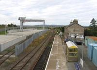 No rural idyll these days. Georgemas Junction now features a mighty 110-tonne gantry crane for road-rail transfer of contaminated materials from the decommissioned Dounreay nuclear site. As seen here on 26th August 2015, the redundant former up platform has been lost to the new facility.<br><br>[David Spaven&nbsp;26/08/2015]