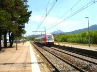 View south along the lengthy platforms at Argeles Sur Mer station as the long distance service from Cerbere to Avignon, consisting of a 4 coach 27500 class EMU, with driving vehicle 27866 leading, runs into the station on 5 August 2015.<br><br>[David Pesterfield&nbsp;05/08/2015]