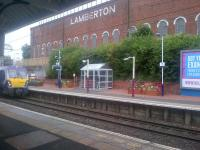 NHS planters on the eastbound platform at Coatbridge Sunnyside on 8 September 2015, with the Lamberton Building in the background. The train arriving is the 0910 Helensburgh Central - Edinburgh Waverley.<br><br>[John Yellowlees&nbsp;08/09/2015]