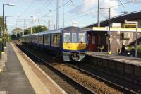 Northern Electrics unit 319386 calls at Broad Green on 09 October with a service to Liverpool Lime Street. The station is on the route of the Liverpool and Manchester Railway. On the right is the western end of the M62 motorway. <br><br>[John McIntyre&nbsp;09/10/2015]