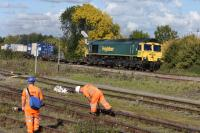 66589, on an eastbound container train, passes a Network Rail gang engaged on track maintenance in the sidings at Didcot on 081015. <br><br>[Peter Todd 08/10/2015]