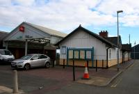 The entrance to Pwllheli station at the north end of the building on 14th October 2015. The building on the left is a discount store built on the site of the north part on the former island platform and its release road.<br><br>[Colin McDonald&nbsp;14/10/2015]