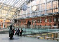 There are three iconic artworks in St Pancras, all visible in this track level image. In the foreground Sir John Betjeman is doing what most visitors to the station do. Behind is the 9m high <I>Meeting Place</I> statue, otherwise known as <I>The Lovers</I>, and above that is the Dent Clock, with its black replica known as <I>One More Time</I> hanging in front of it. <br><br>[Mark Bartlett&nbsp;11/09/2015]