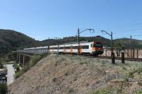 Two RENFE Class 447 EMUs have just left Colera station and rumble onto the viaduct heading south. The bridge, high above the town itself, is one where the rails run across the open girders but there is no decking.<br><br>[Mark Bartlett&nbsp;19/09/2015]