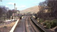 The view north over Abington station in March 1966, some 14 months after closure. Photographed from the bridge carrying Station Road, which continues towards the village on the left. The station building has since been replaced by a maintenance compound and the platforms by passing loops. [See image 5602]<br><br>[John Robin&nbsp;25/03/1966]