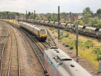 A Cross Country Voyager, running from Penzance to Glasgow, passes a TPE 185, bound for Manchester Airport, just to the south of York station. On the right, a rake of Freightliner coal hoppers has been stabled in the Holgate sidings for the weekend.<br><br>[Mark Bartlett&nbsp;18/07/2015]