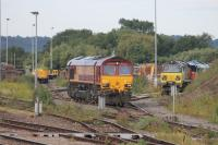 DBS 66200 eases out of the stabling sidings in Westbury Yard on 25th July 2015. To the right, Colas 70810 stands at the head of a line of stabled Class 70 and Class 66 locos in this view taken from the station platform.<br><br>[Mark Bartlett&nbsp;25/07/2015]