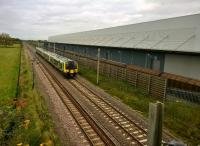 Only eight months ago [see image 50466], this Eddie Stobart warehouse was just a steel frame. Now it is in use, ready to exchange freight with the line of Cargowaggons on the siding. The 350 is heading for London via Northampton.<br><br>[Ken Strachan&nbsp;23/10/2015]