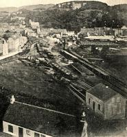 The high level goods yard above Oban in a view looking north east. The approach to the pier can't be seen - it is in a cutting beyond the cottage seen in the foreground. There is an engine shunting at the far end of the yard.<br><br> <br><br> The cattle market is to the right. The incomplete and abandoned hydro is prominent on the hillside above the town.<br><br> <br><br> The building at the bottom right is the coaling canopy on one of the approach roads to the engine shed (out of shot to the right) - publisher touching up of this postcard view has converted it into what looks like a house. This was removed when the coaling plant was installed by the LMS. <br><br> <br><br> This area has been redeveloped - the yard closed in 1969 (an oil siding surviving until the early 1990s) and the cattle market has been relocated further south.<br><br>[Ewan Crawford Collection&nbsp;//]