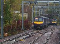 Having just cleared the newly installed crossover which is part of the Anniesland EGIP Works, EMU 320312 heading for Milngavie is just about to pass 320306 bound for Edinburgh on a rainy 10th November 2015.<br><br>[Colin McDonald&nbsp;10/11/2015]
