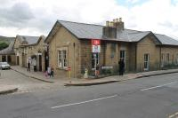 Part of Glossop station has been tastefully incorporated into a supermarket, built in matching stone, and the railway now only occupies the extreme right of the building. Everything beyond the arched door under the blue sign is now in retail use. The station is still staffed and enjoys a 30 minute frequency service to Manchester.  <br><br>[Mark Bartlett&nbsp;01/09/2015]
