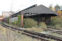 The abandoned Mersey Railway carriage depot at Birkenhead Central (BC), as seen from the station platform in November 2015. The third rails have been removed from the depot tracks but the siding alongside is still live and appeared to be used occasionally. The depot sits in a deep hollow so redevelopment of the site may not be straightforward. EMU maintenance on the Wirral side of the Mersey is now concentrated at Birkenhead North (BD).<br><br>[Mark Bartlett&nbsp;16/11/2015]