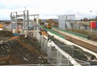 View over part of the construction site which will become the new Edinburgh Gateway interchange on 11 November 2015, seen from the down side of the line. The 0941 Inverness - Edinburgh is about to run south through the platforms while in the background the 1300 Edinburgh - Dundee is heading for the Forth Bridge.<br><br>[John Furnevel&nbsp;11/11/2015]